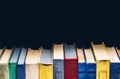 Bunte Bücher in Folge in der Bibliothek oder in der Buchhandlung auf schwarzem Hintergrund mit Kopie-Raum Stockfotografie