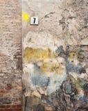 Bunte Backsteinmauer und Platte mit einer Nr. sieben Stockfotografie