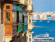 Bunte Balkone von Valletta mit touristischem Boot - Malta stockfotos
