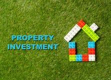 Bunte Bauklotzhaus und -text Eigentums-Investition geschrieben auf Gras in Wohnungsmarktgeschäft stockfotos