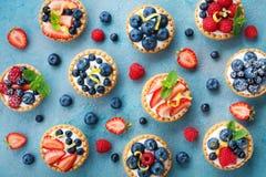Bunte Beerentartlets oder -kuchen für Küchenmuster Gebäcknachtisch von oben lizenzfreies stockfoto