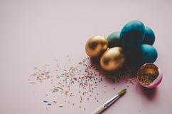 Bunte blaue und goldene Ostereier mit dem Süßigkeitenbesprühen Stockbild