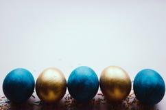 Bunte blaue und goldene Ostereier mit dem Süßigkeitenbesprühen Stockfotos