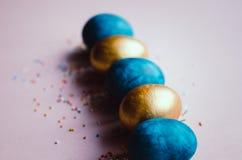 Bunte blaue und goldene Ostereier mit dem Süßigkeitenbesprühen Lizenzfreie Stockfotos