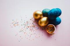 Bunte blaue und goldene Ostereier mit dem Süßigkeitenbesprühen Stockfotografie