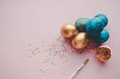 Bunte blaue und goldene Ostereier mit dem Süßigkeitenbesprühen Stockbilder