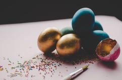 Bunte blaue und goldene Ostereier mit dem Süßigkeitenbesprühen Lizenzfreies Stockfoto
