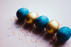 Bunte blaue und goldene Ostereier mit dem Süßigkeitenbesprühen Stockfoto