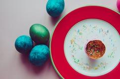 Bunte blaue und grüne Ostereier mit den Süßigkeiten, die auf Platte besprühen Lizenzfreies Stockbild