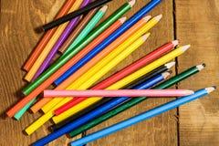 bunte Bleistifte auf altem Holztisch Lizenzfreies Stockfoto
