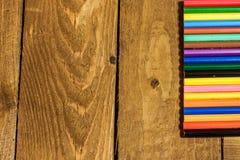 bunte Bleistifte auf altem Holztischsatz Stockfoto
