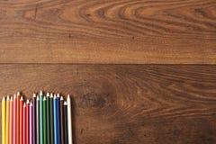 Bunte Bleistifte auf dem braunen Holztischhintergrund Feld von farbigen Bleistiften über Holz mit freiem Raum für Text Lizenzfreies Stockbild