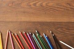 Bunte Bleistifte auf dem braunen Holztischhintergrund Feld von farbigen Bleistiften über Holz mit freiem Raum für Text Lizenzfreie Stockfotos