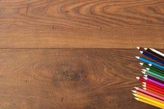 Bunte Bleistifte auf dem braunen Holztischhintergrund Feld von farbigen Bleistiften über Holz mit Kopienraum Lizenzfreie Stockbilder