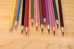 Bunte Bleistifte auf hölzernem Hintergrund Stockbild