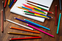 Bunte Bleistifte auf Holztisch mit Papier Beschneidungspfad eingeschlossen Lizenzfreie Stockfotos