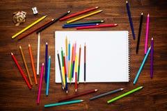 Bunte Bleistifte auf Holztisch mit Papier Beschneidungspfad eingeschlossen Stockfotografie
