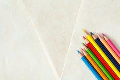 Bunte Bleistifte auf Papierhintergrund Lizenzfreie Stockfotografie