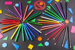 Bunte Bleistifte in den Kreisen und geometrische Zahlen auf der Tafel Stockfoto