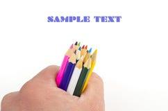 Bunte Bleistifte in der Hand auf Weiß Lizenzfreies Stockfoto