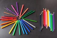 Bunte Bleistifte in der Reihe auf der schwarzen Schultafel als Hintergrund, Konzept zurück zu Schule Lizenzfreies Stockbild