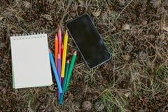 Bunte Bleistifte des Notizbuches und des Stapels auf Waldlage Stockbild