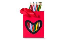 Bunte Bleistifte in einer roten Tasche mit Herzen formen Stockbilder