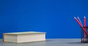 Bunte Bleistifte für das Zeichnen und Buch auf Kopienraumhintergrund Stockfotos