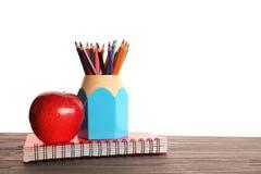 Bunte Bleistifte im Halter, im roten Apfel und im Übungsbuch Stockfotografie