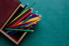 Bunte Bleistifte im Kasten auf Schreibtisch Stockbild
