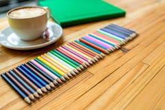 Bunte Bleistifte mit Büchern und Kaffee Stockfotos