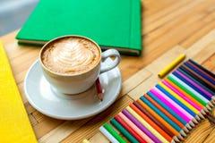 Bunte Bleistifte mit Büchern und Kaffee Stockbild