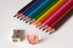 Bunte Bleistifte mit Bleistiftspitzer auf einem Blatt der weißen Pappe lizenzfreies stockbild