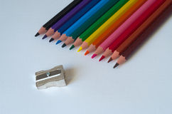 Bunte Bleistifte mit Bleistiftspitzer auf einem Blatt der weißen Pappe Stockbild