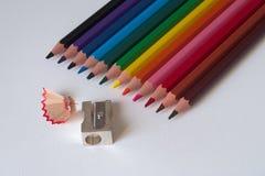 Bunte Bleistifte mit Bleistiftspitzer auf einem Blatt der weißen Pappe Lizenzfreie Stockfotos