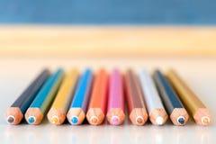 Bunte Bleistifte mit einer unscharfen Tafel Stockbilder