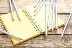 bunte Bleistifte mit Notizbuch Stockfoto