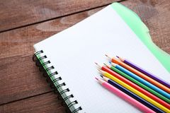 bunte Bleistifte mit Notizbuch Lizenzfreie Stockfotografie