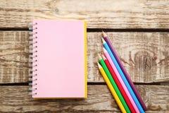 bunte Bleistifte mit Notizbuch Stockfotos