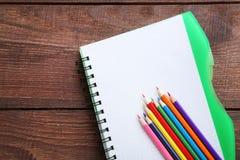 bunte Bleistifte mit Notizbuch Lizenzfreie Stockfotos