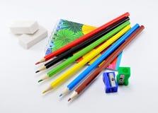 Bunte Bleistifte mit Radiergummis, Bleistiftspitzer und Notizblock auf weißem Hintergrund Lizenzfreie Stockfotografie