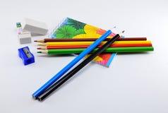 Bunte Bleistifte mit Radiergummis, Bleistiftspitzer und Notizblock auf weißem Hintergrund Lizenzfreies Stockbild