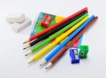Bunte Bleistifte mit Radiergummis, Bleistiftspitzer und Notizblock auf weißem Hintergrund Lizenzfreie Stockfotos