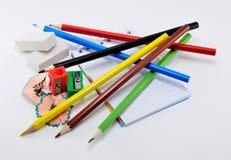 Bunte Bleistifte mit Radiergummis, Bleistiftspitzer und Notizblock auf weißem Hintergrund Lizenzfreie Stockbilder