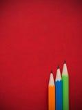 Bunte Bleistifte setzten an rote lederne Buchbucht Stockbilder