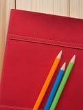 Bunte Bleistifte setzten an rotes Tagebuchbuch auf den hölzernen Schreibtisch Lizenzfreie Stockfotos