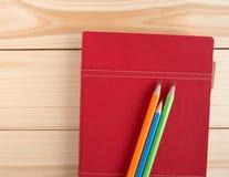 Bunte Bleistifte setzten an rotes Tagebuchbuch auf den hölzernen Schreibtisch Stockfotos