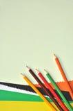 Bunte Bleistifte und Farbenpapier Stockfotografie