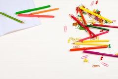 Bunte Bleistifte und Filzstifte, Büroklammern, Briefpapiernägel, smilie Mappen auf weißem hölzernem Hintergrund Stockbilder