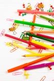 Bunte Bleistifte und Filzstifte, Büroklammern, Briefpapiernägel, smilie Mappen auf weißem hölzernem Hintergrund Stockbild